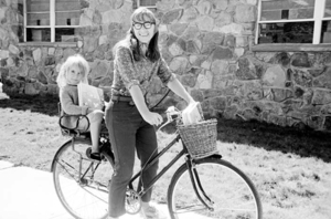 """Mary Hayes on a bike, with her young daughter Jess Bates on the back. She is distributing her cookbook, """"Aspen Potpouri"""", September 1968. She is next to the Post Office on Spring Street."""