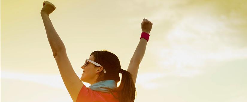 woman raises her hands in triumph