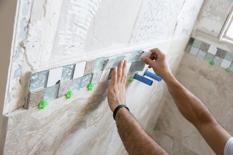 Tile border made up of small square tiles in glass, metal and stone are being adhered to the wall of a shower. Tiles are a very popular feature for both modern shower's, with <a href=