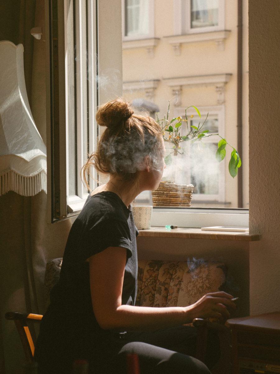 Woman smoking cannabis by window