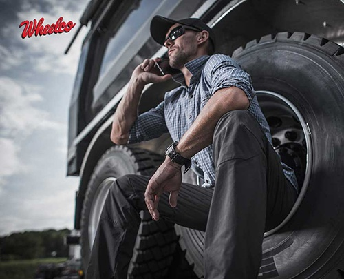 Man Sitting Next to Heavy Duty Truck