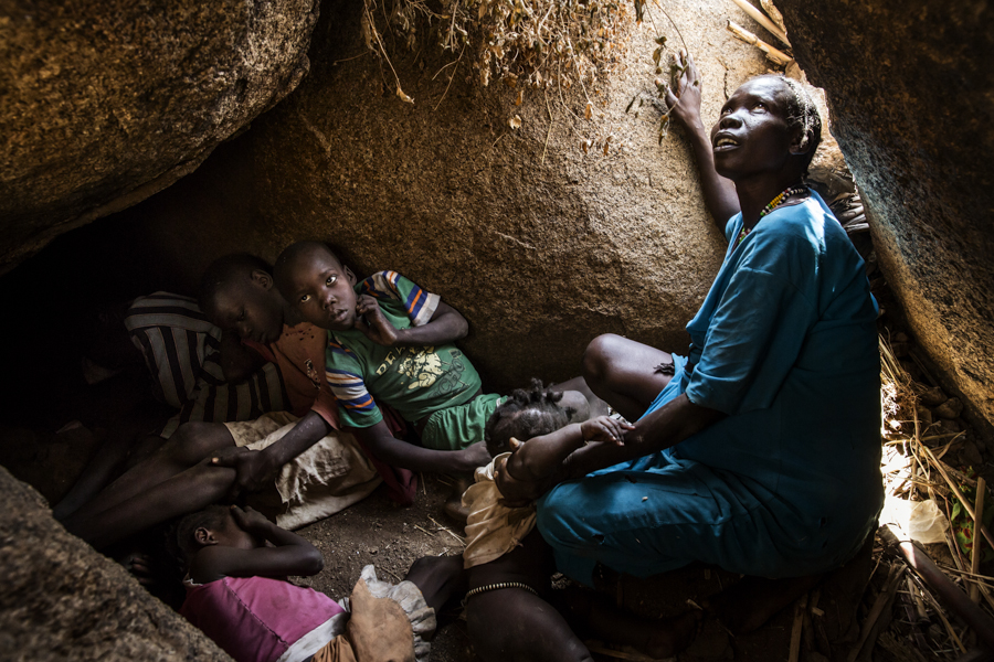 Africa, Sudan, South Kordofan. Semma Kafi Gelem, 30 years old, pregnant of her eighth child, is seen as she seeks shelter for her and the children, from an Antonov bomber flying over the area of Buram. 07th Dec 2013 © Marco Gualazzini / LUZ