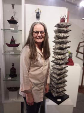 <p>Linda Korstad in front of her quirky, fun ceramic art. </p>