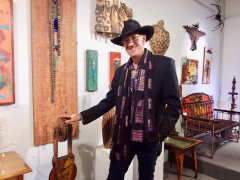 <p>KIT CARSON in front of his wonderful display of metal art.</p>