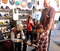 <p>Our shoemaker, Mark Carter, fitting Peggy with her new shoes while father-in-law, John looks on. Granddaughter Zoe in perpetual motion!</p>