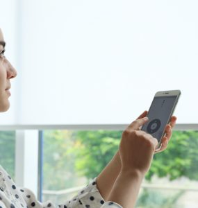 Woman using smart home application on phone to control window blinds indoors