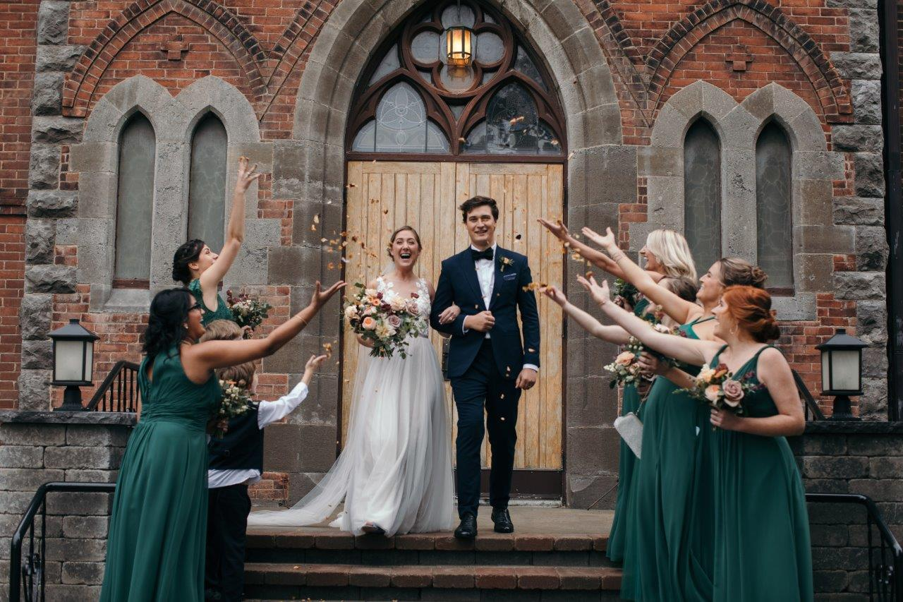 Bride and groom exit the church with confetti thrown by the bridesmaid