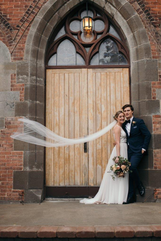 Bride and groom pose outside the church with the bride's veil flowing in the wind