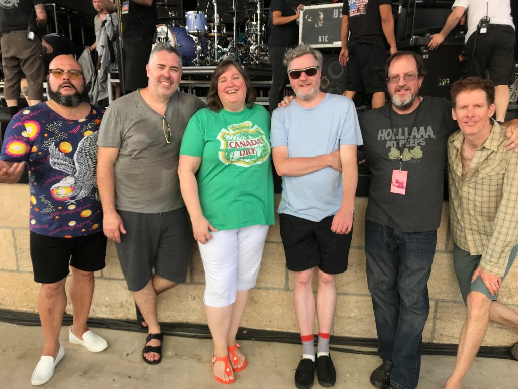 Photo Caption: Barenaked Ladies Band with Lisa Byers & her husband, Thomas Left to Right – Tyler Stewart (drums), Ed Robertson (lead singer), LISA BYERS, Kevin Hearn (keyboards, guitar, accordion, etc.), Thomas Byers, Jim Creeggan (bassist).