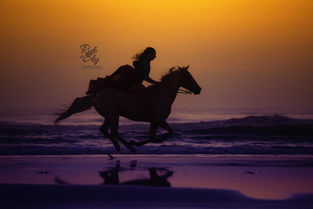 Girl riding horse on the beach captured at a horse photography workshop
