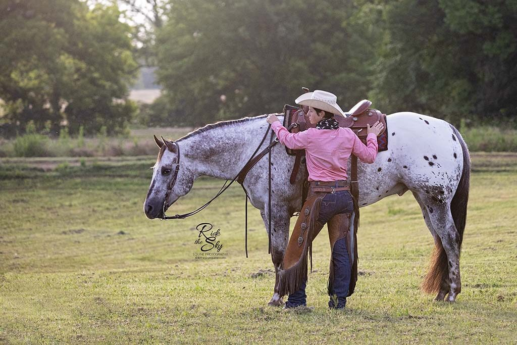 Cowgirl and Appaloosa Horse in field