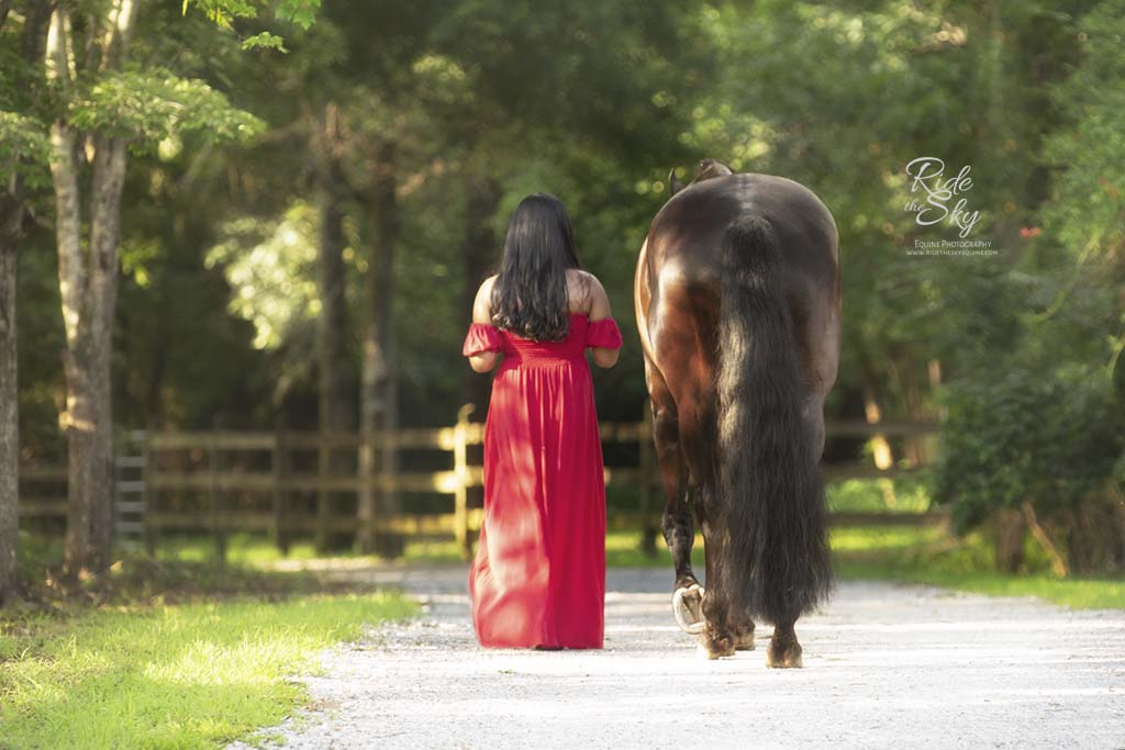 Girl in long red dress walking down path next to horse in Chattanooga, TN