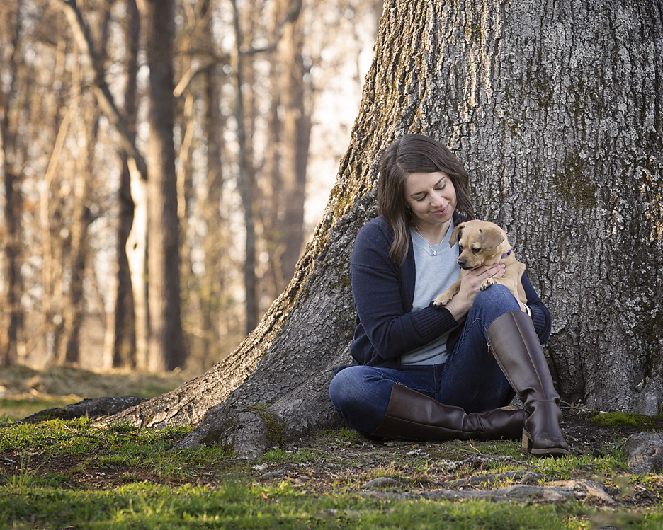 Woman and dog sitting next to tree at Enterprise South Nature Park in Chattanooga