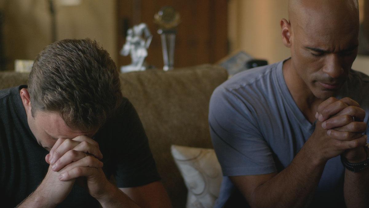 Bradley Snedeker and Darren Dupree Washington praying together.