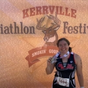 A record number of triathletes registered for the 2019 Kerrville Triathlon, including this female sprint finisher posting in front of the Kerrville Tri sign.