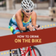 Female cyclist rides on the bike course during the Kerrville Triathlon. Text on design reads How to Drink on the Bike. Learn more about hydrating while cycling at https://kerrvilletri.com/2020/09/hydrating-while-cycling/