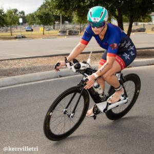 Cyclist takes the corner for the final turn before transition at the Kerrville Triathlon. Credit Ed Sparks.