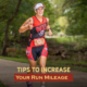 Female triathlete runs next to the Guadalupe River during the Kerrville Triathlon. Text on design reads Tips to Increase Your Run Mileage. Learn more at https://kerrvilletri.com/2020/12/increase-your-run-mileage/