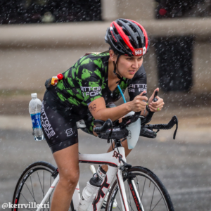 Cyclist rides during the rain with her hydration bottles visible during the Kerrville Triathlon. Credit Ed Sparks.