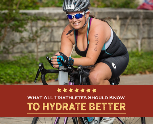 Female triathlete smiles for the camera while riding her bike. Text on design reads What All Triathletes Should Know to Hydrate Better. Learn more at https://kerrvilletri.com/2021/03/hydrate-better/