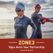 Two triathletes prepare for an open water swim in their Zone3 wetsuits. Text on design reads Zone3 Signs Multi-Years Partnership. Learn more at https://kerrvilletri.com/2021/05/zone3-usa-partnership/