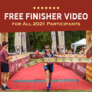 Female triathlete crosses the Kerrville Triathlon finish line with her arms in the air. Text on design reads Free Finisher Video for all 2021 Participants. Learn more about the free, personalized finish line video at https://kerrvilletri.com/2021/07/free-personalized-finish-line-video/