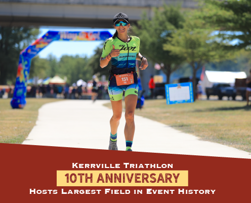 Female runner has a huge smile during the run portion of the 2021 Kerrville Tri. Text on design reads Kerrville Triathlon 10th Anniversary Hosts Largest Field in Event History. Read more at https://kerrvilletri.com/2021/09/largest-field-in-event-history/