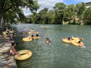 Image of triathletes and their friends and family floating in the Guadalupe River at the finish line festival. Floating is back for the 10th-anniversary celebration.