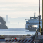 US, Washington State, Seattle ferry arrives Bainbridge with first load of bicyclists for Chilly Hilly race. Seattle skyline in morning fog