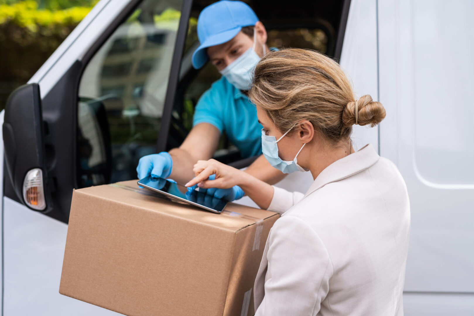 Prevention masks are new safety measures. Young woman receiving package from the delivery man on a van