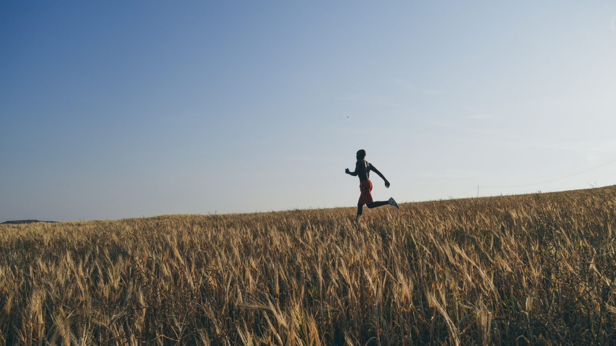 man in black jacket and black pants running on brown grass field during daytime