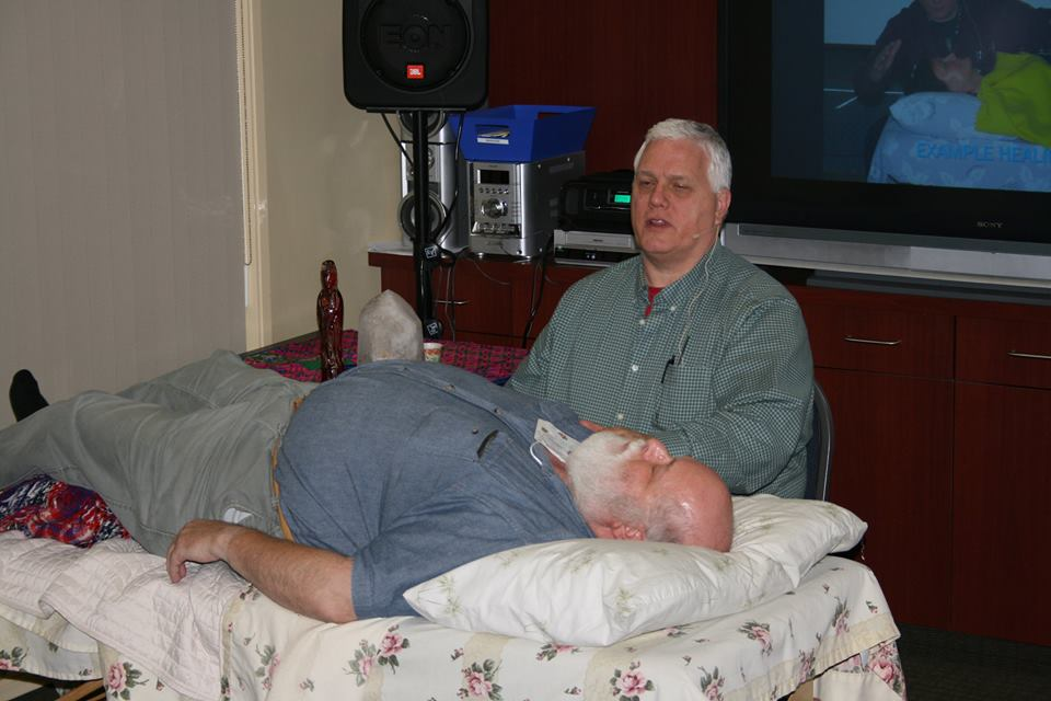 Dr Richard Jelusich performing energy work on a speaking engagement participant