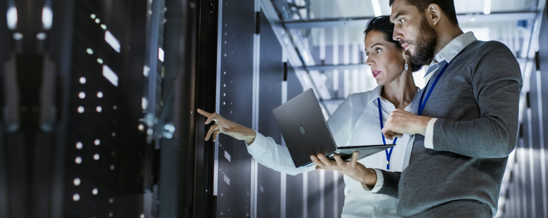 Male IT Specialist Holds Laptop and Discusses Work with Female Server Technician