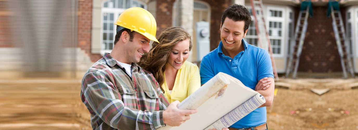 Construction: Young Couple Look At Home Plans with Builder