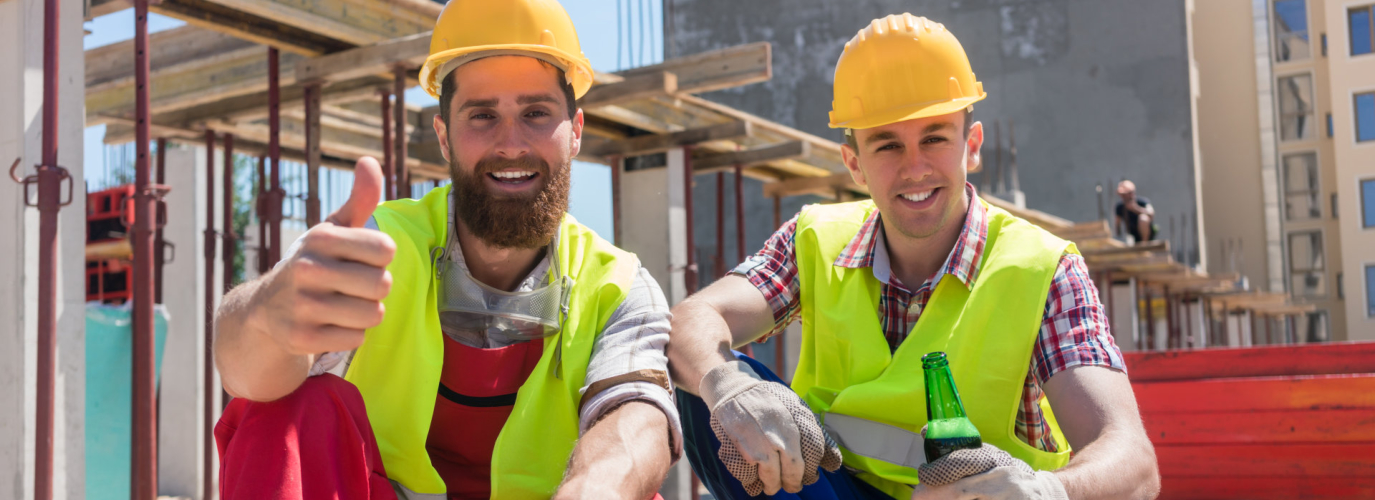 Two,Young,Workers,Smiling,,While,Drinking,A,Cold,Alcoholic,Or