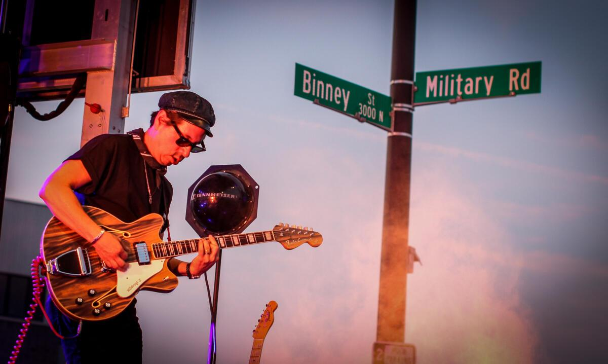 With the Military Road sign in the background, Adrian Quesada performs with Black Pumas at Waiting Room Outdoors in Omaha.