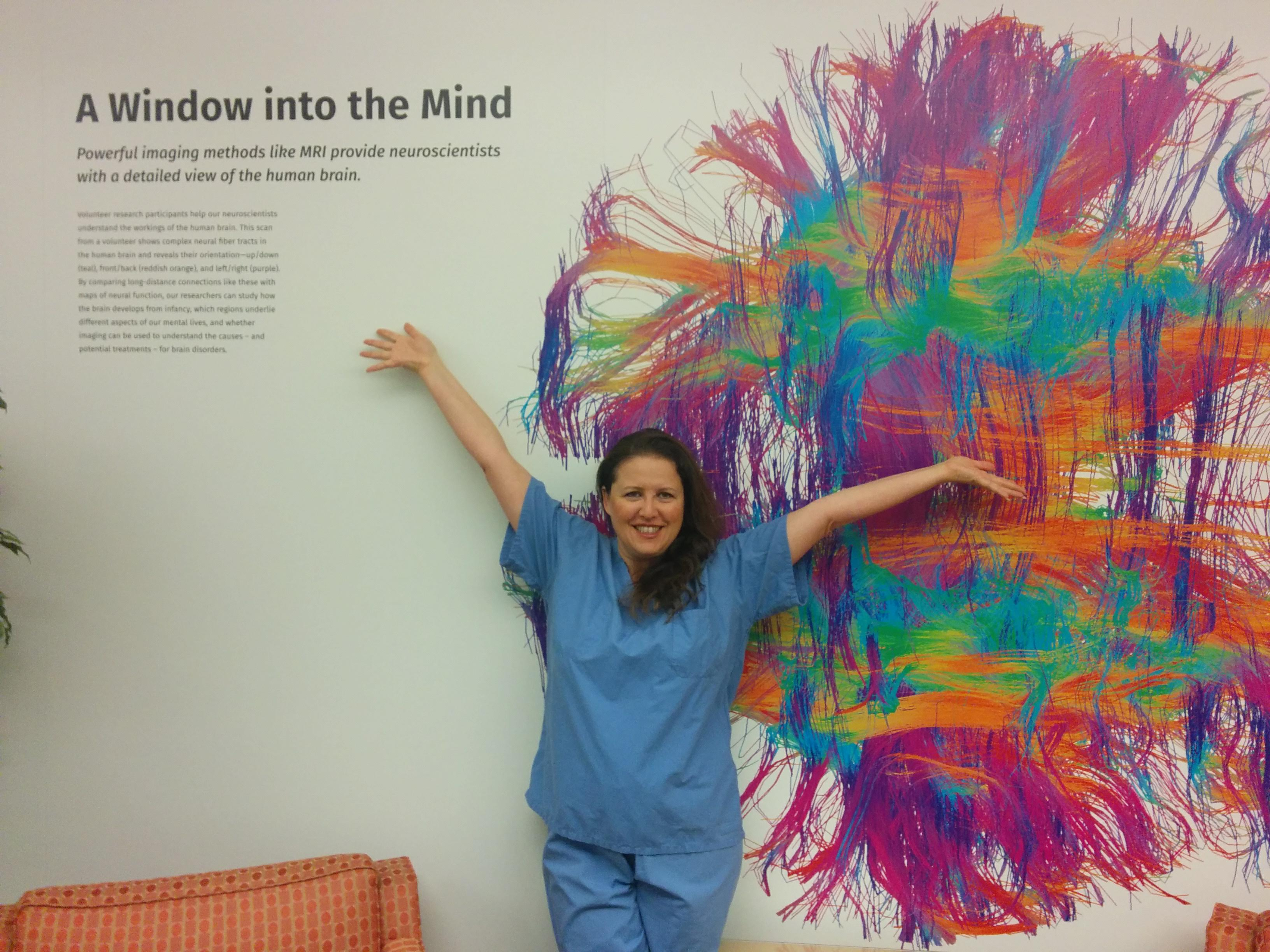 Susanna Zaraysky in scrubs in front of painting of the brain