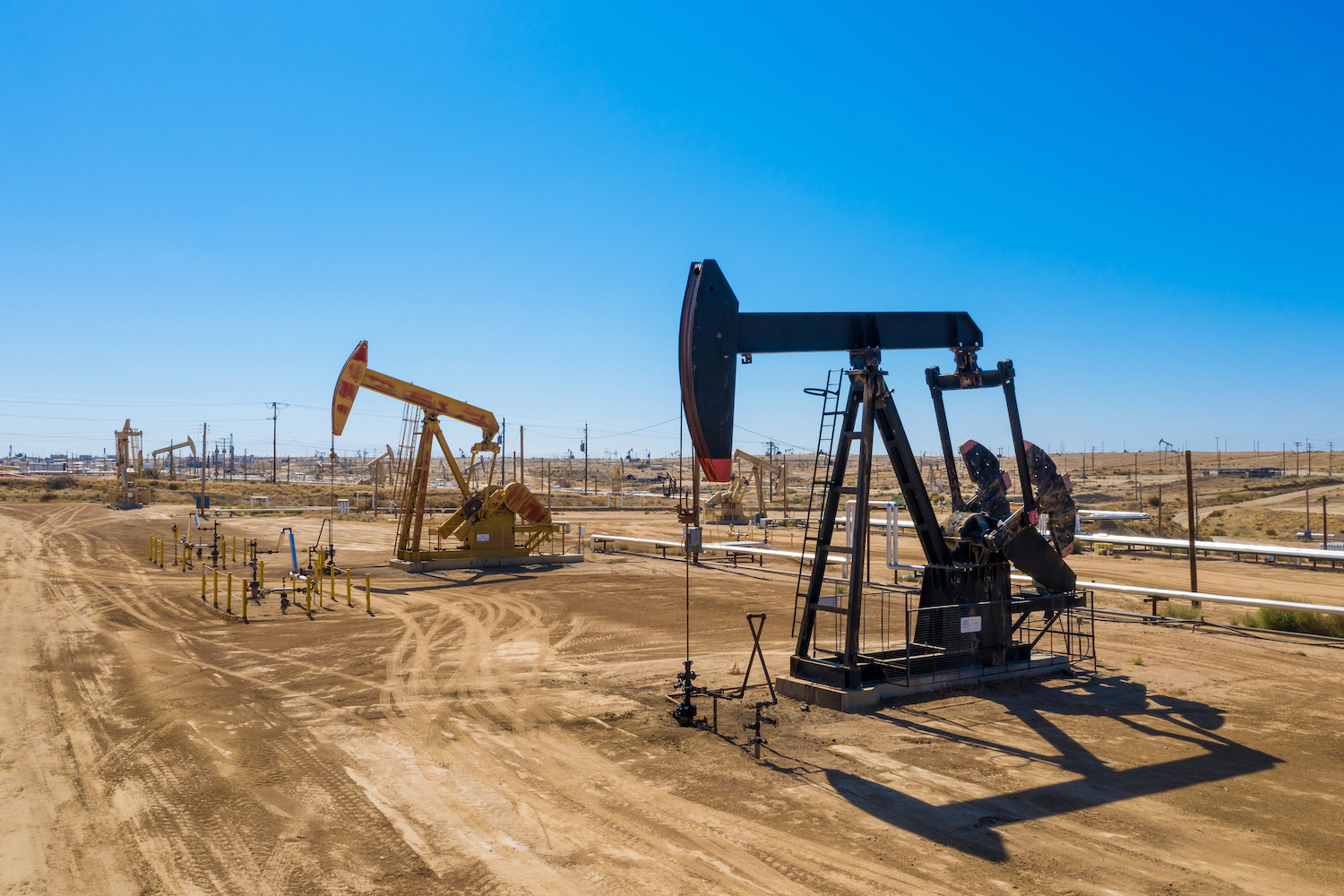 oil derrick pumps in a sandy field during the day with blue sky