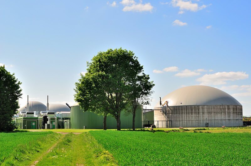 biogas plant in field with trees surrounded by grass