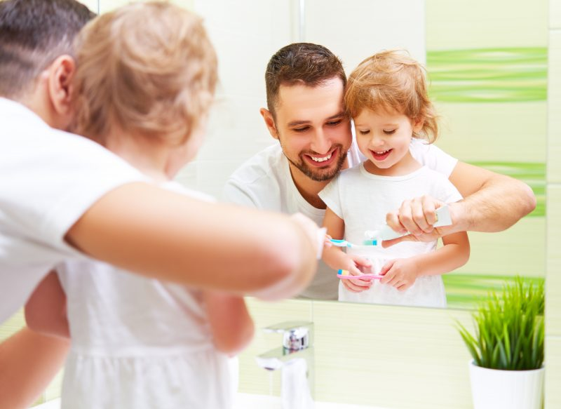 Dad Helping Kid Brush Teeth