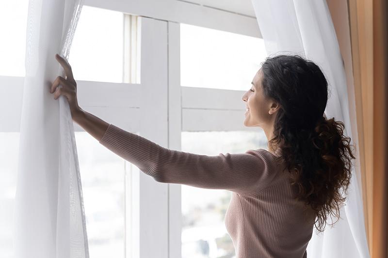 Smiling Woman Opening Curtains In Morning, Enjoying Sun
