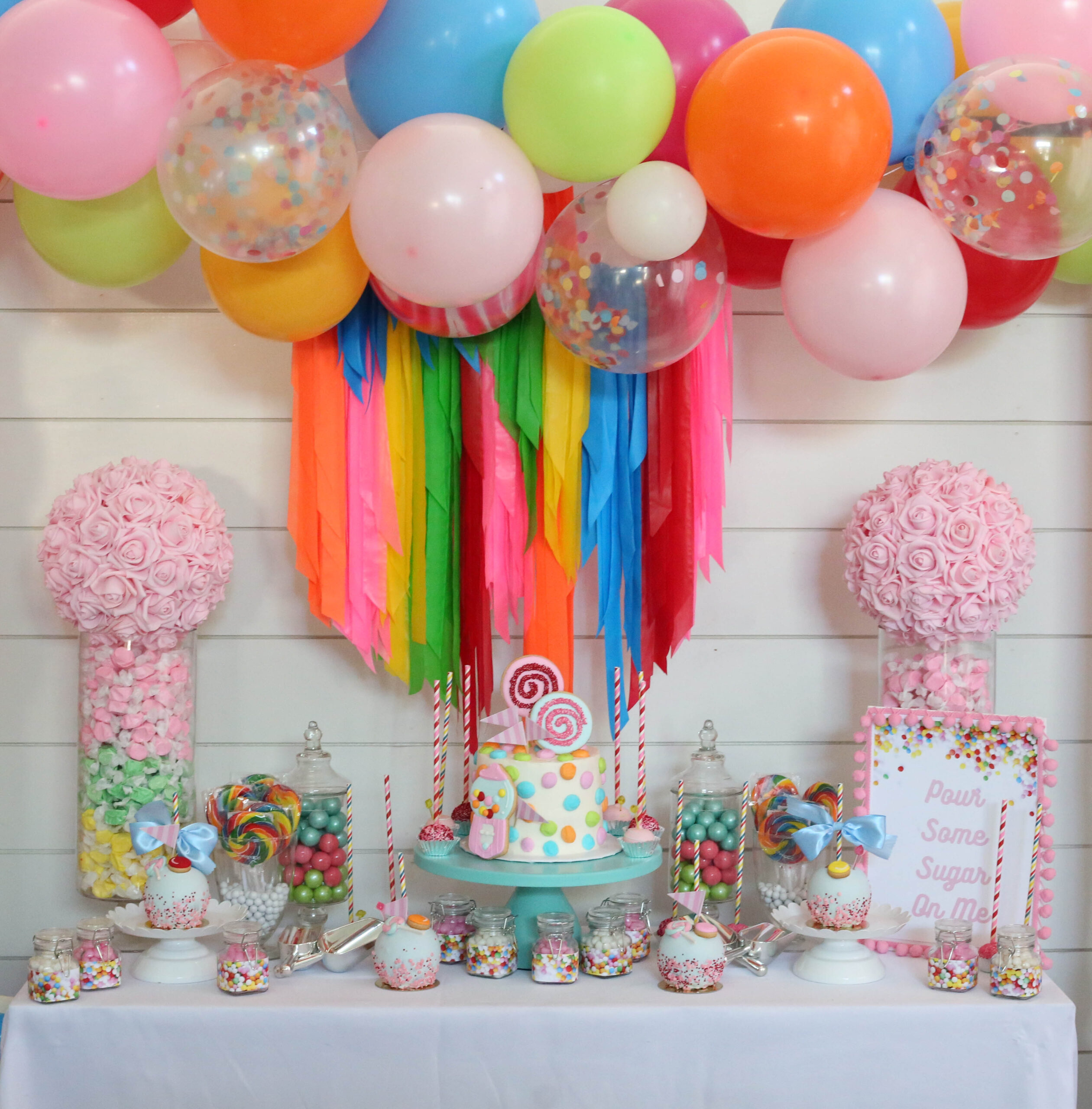 candy themed party backdrop display with balloon garland and rose balls