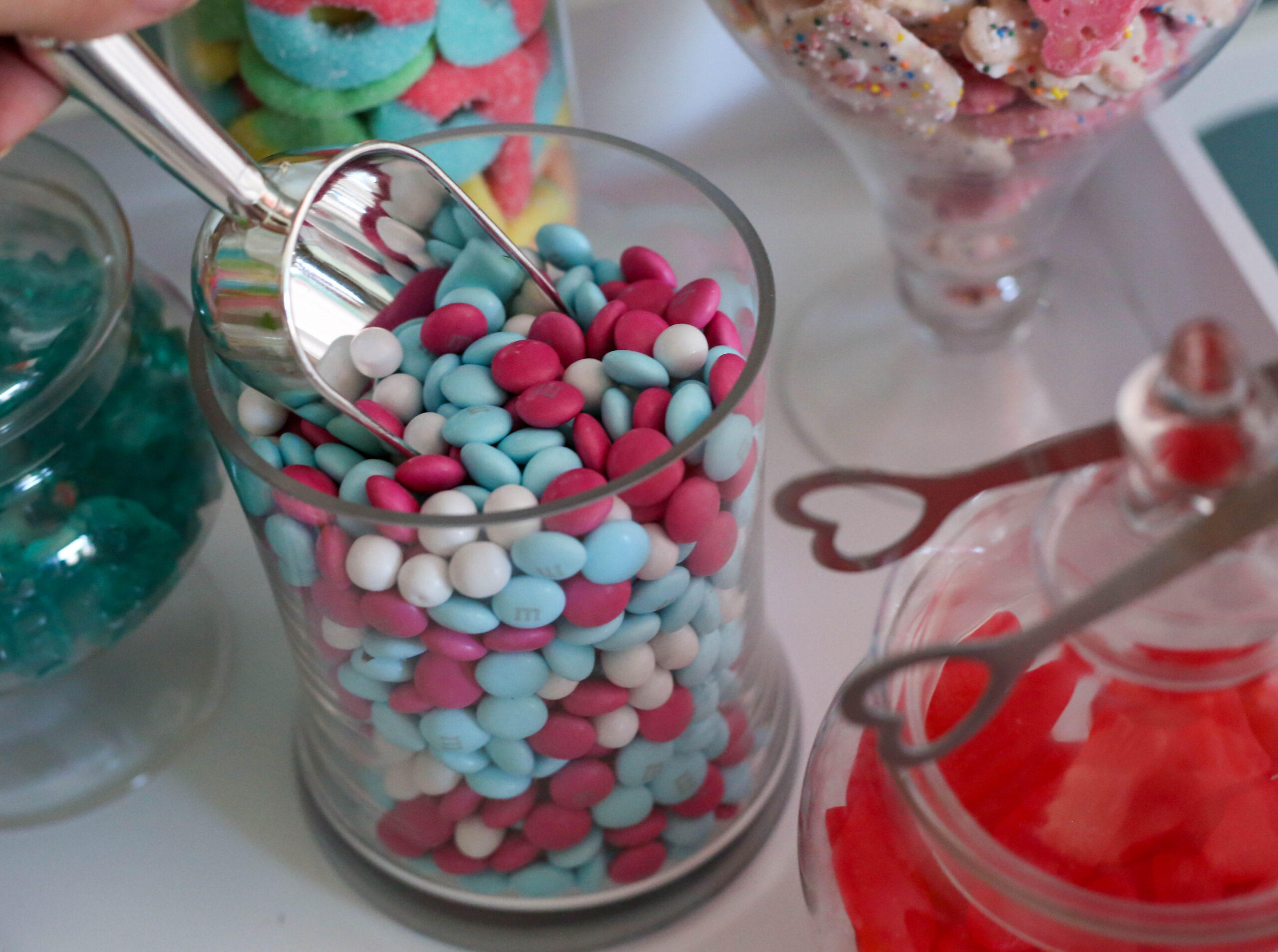m&ms candy at a candy theme party in a glass candy jar with silvertone scoop