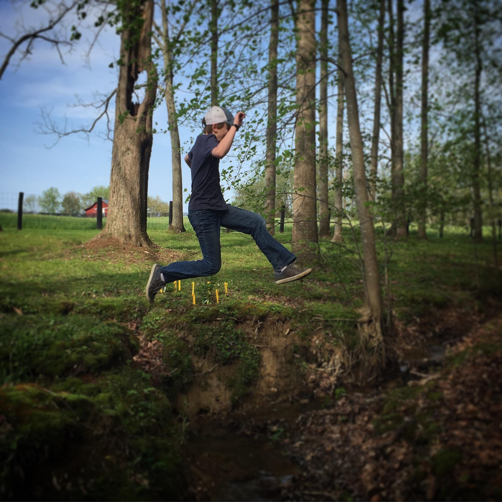Boy jumping over a creek.