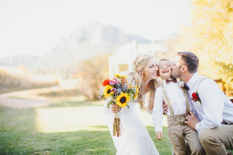 A bride and groom stand together kissing their son at sunset wearing a white dress and formal wear for this Lower Lake Ranch wedding photography session