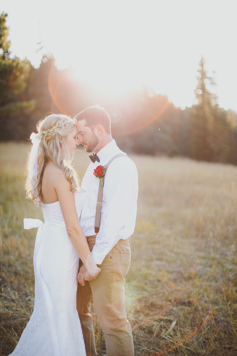 A bride and groom stand together posing at sunset wearing a white dress and formal wear for this Lower Lake Ranch wedding photography session