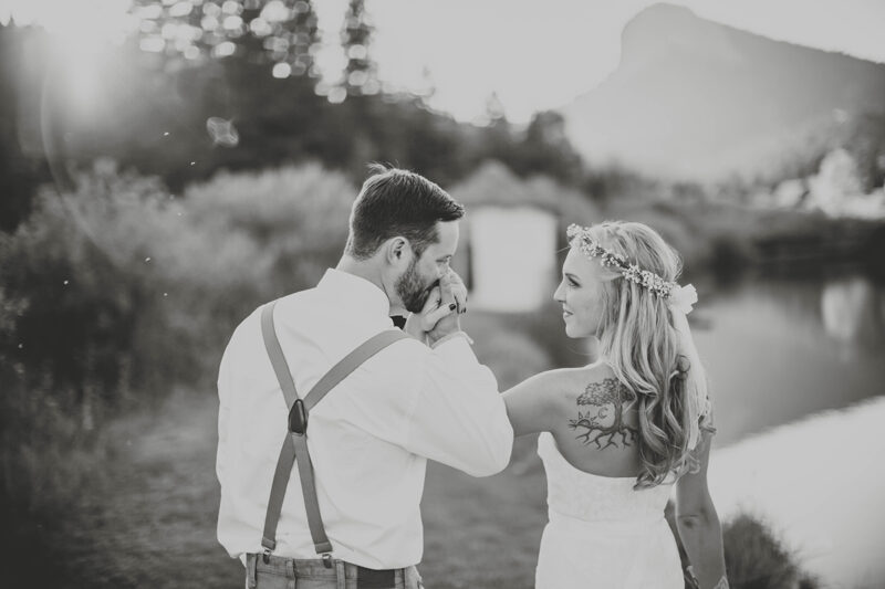 A bride and groom walk together holding hands at sunset wearing a white dress and formal wear for this Lower Lake Ranch wedding photography session
