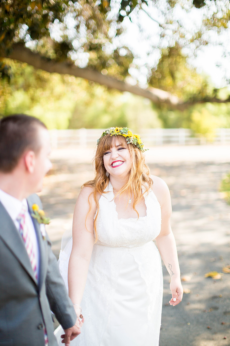 A bride and groom walk together wearing a flower crown and a white dress and a gray suit for this Camarillo Ranch wedding photography session
