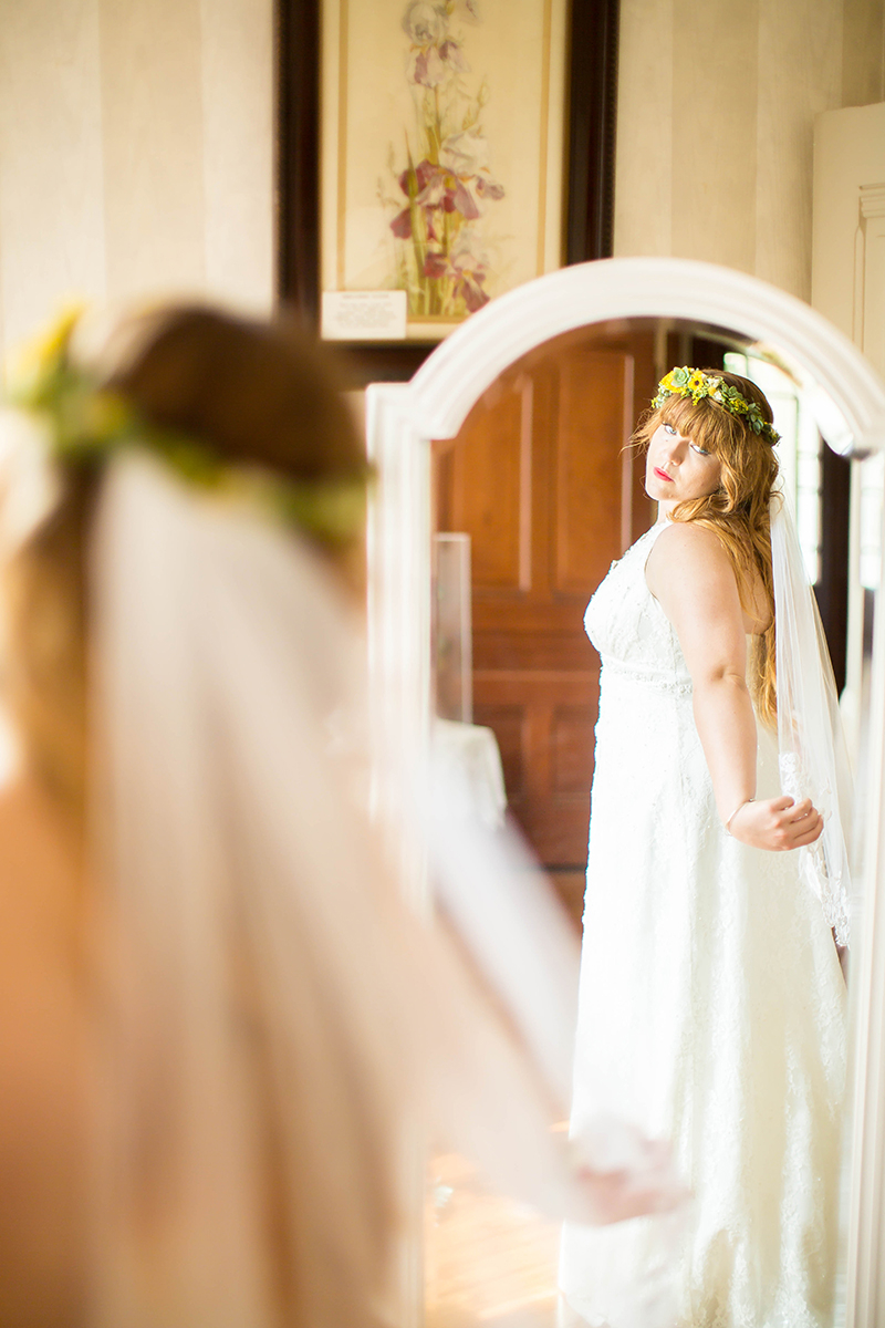 A bride looking in the mirror wearing a flower crown and white dress for this Camarillo Ranch wedding photography session