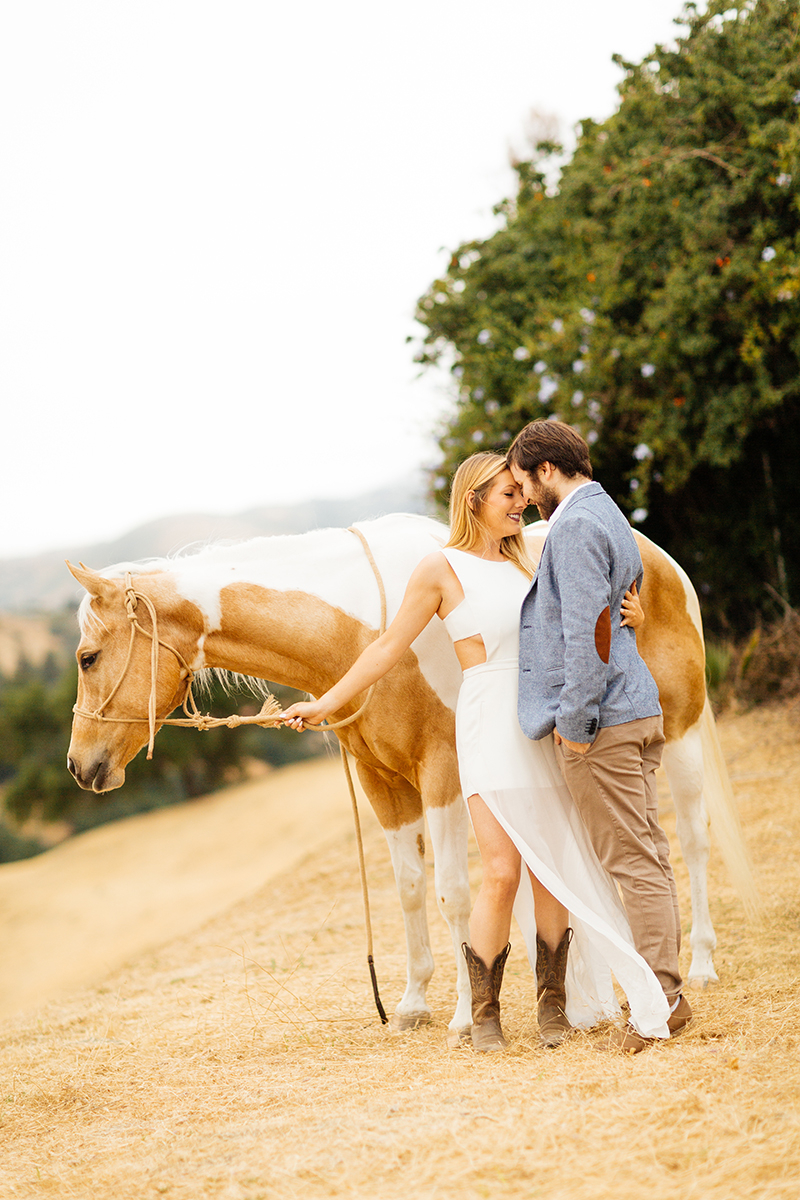 An engaged couple hold each other close with a horse on the hillside for this Granada Hills engagement photography session